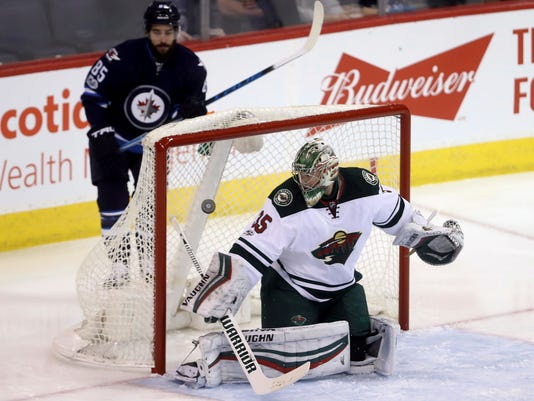 Winnipeg Jets' Patrik Laine, not shown, scores on Minnesota Wild goalie Darcy Kuemper (35) as Mathieu Perreault (85) skates behind the net during the first period of an NHL hockey game Tuesday, Feb. 28, 2017, in Winnipeg, Manitoba. (Trevor Hagan/The Canadian Press via AP)