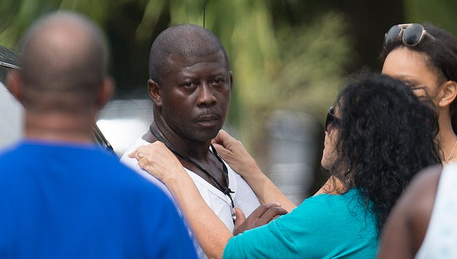 Kendrick Moore is comforted at the scene of the murder of Rodney Greenlee at the itersection of Cranford Avenue and Dr. Ella Piper Way in Fort Myers.  He was later arrested in Greenlee's death.  He was charged with second degree murder, possession of a firearm by convicted felon