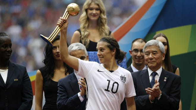 Carli Lloyd holds the Golden Ball trophy for being the tournament MVP as she stands with tournaments officials after the team beat Japan in the FIFA Women's World Cup soccer championship in Vancouver, British Columbia, Canada, Sunday, July 5, 2015.