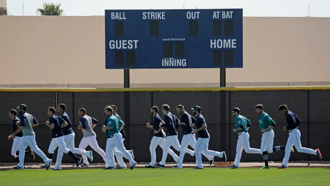 Players for the Seattle Mariners run sprints during spring training baseball practice Monday, Feb. 22, 2016, in Peoria, Ariz.