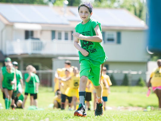 "Chase Schweiger, 10, a fifth-grader at Helen L. Beeler Elementary School in Marlton, competes in a race during the school's field day on Friday.  Chase suffered a massive stroke three years ago and he celebrated his three year ""Stroke-aversary"" during the field day event."