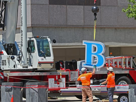The sign on the BMO Harris Bradley Center starts to come down.  Workers unbolt the letters, and then they are lowered to the ground by crane and loaded on a truck.