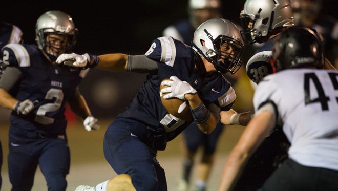 Reitz's Calvin Brinton (6) carries the ball through the Terre Haute South defense during Friday night's game.