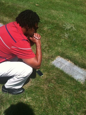 Ernest Green looks at his father's grave.