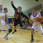 Marathon's Ryan Tillotson, center goes airborne after colliding with Trumansburg's Mike Gorton, left, as Andrew Stewart, right, drives towards the basket during the Section 4 Class C first-round game, held Wednesday night in Trumansburg. The Trumansburg Blue Raiders won 76-49.