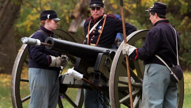 From left, Karen Nelson, Gary Coon and Wendi Parisi, Reynolds' Battery re-enactors, prep the cannon to fire Saturday.