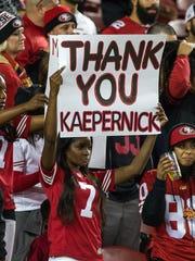 "A San Francisco 49ers fan holds a ""thank you Kaepernick"""