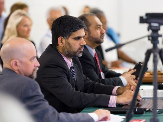 Naveed Baqir (middle) and Muqtadar Khan (right) listen to a debate hosted by Delaware Council on Global and Muslim Affairs featuring U.S. House candidates.