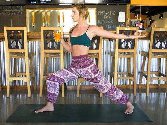 Hannah Walt poses with a pint of beer at Metazoa Brewing. The brewery hosts a yoga class every Sunday.