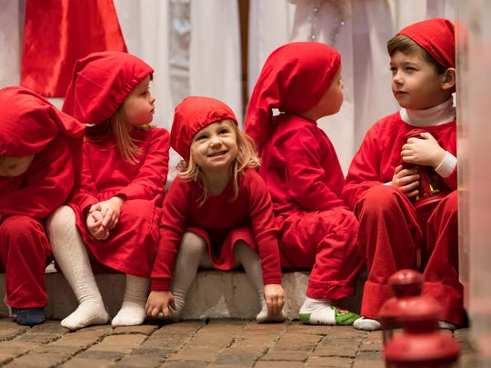 Tomta, children in red outfits, play during the Sankta Lucia procession at Old Swedes Church in Wilmington on Sunday afternoon.
