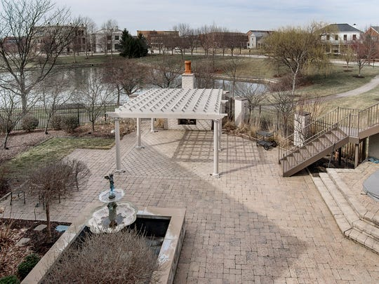 The backyard, as seen from the second-floor balcony, includes a hot tub, fountain, little grass and a water view.