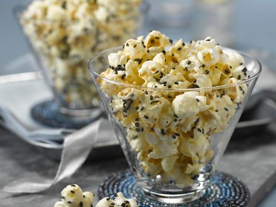 Sesame mustard popcorn is finished with black sesame seeds and kosher salt.