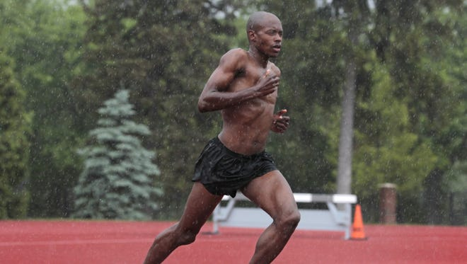 Kip Tisia, the area's top distance runner, gets in some soggy training in the rain at the University of Rochester on June 9, 2015.