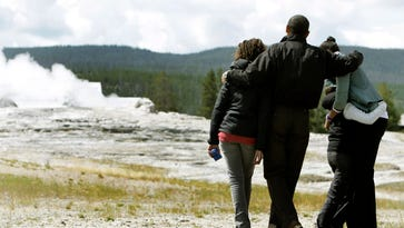 President Obama, wife Michelle Obama, and daughters Malia and Sasha look at the Old Faithful geyser in Yellowstone National Park, Aug. 15, 2009.