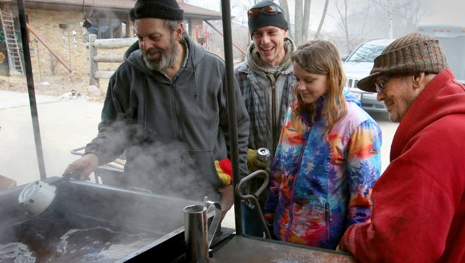 Four generations share a laugh at one of four maple syrup cookers on Creek Hollow Farm, including Charlie Schmitz (right), great-granddaughter Mkayla Schmitz, 11, grandson Adam Schmitz, and son Lavern Schmitz.