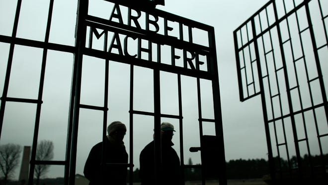 People walk through the gate of the Sachsenhausen Nazi death camp with the phrase 'Arbeit macht frei' (work sets you free) at the eve of the International Holocaust Remembrance Day, in Oranienburg, about 30 kilometers,  (18 miles) north of Berlin, Monday, Jan. 26, 2015.