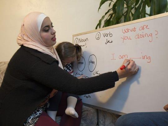 Zana Alattar, holding Lamar Al Alalawa, 2, teaches