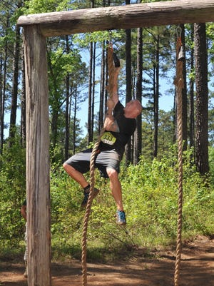 A 2016 Defenders of Liberty Mud Run participant rings a bell after climbing a 15-foot rope at Barksdale Air Force Base. Mud run participants ran a 4-mile course through hilly terrain, conquering 20 obstacles along the way.