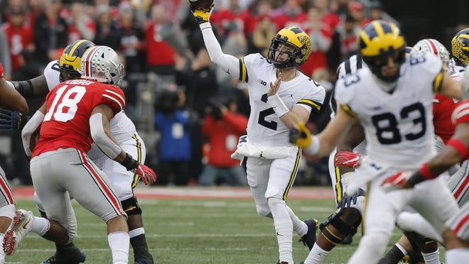 FILE - In this Nov. 24, 2018, file photo, Michigan quarterback Shea Patterson throws a pass against Ohio State during an NCAA college football game in Columbus, Ohio.
