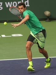 Taylor Fritz runs down a forehand during his win over