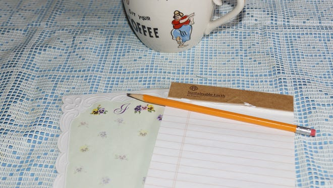 A pencil and a piece of paper accompanied by a cup of coffee.