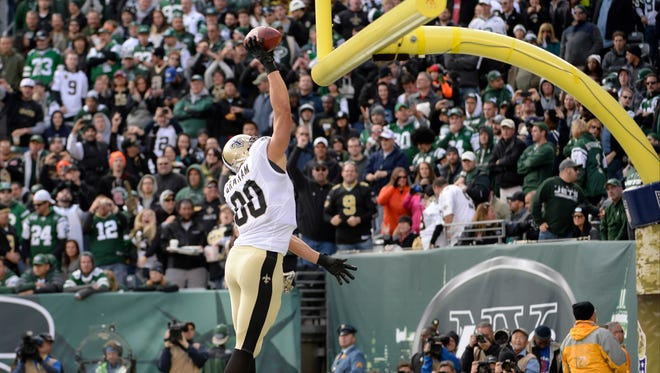 New Orleans Saints tight end Jimmy Graham (80) dunks the ball over the goal post after a touchdown against the New York Jets during the game at MetLife Stadium.