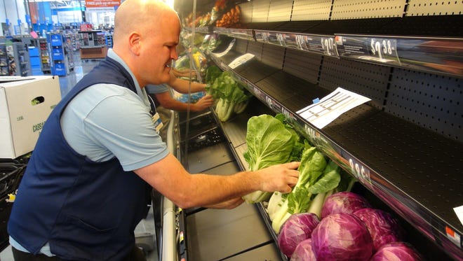 David Mullen of Fairport helps to prepare the BayTowne Walmart for its opening on Wednesday. Mullin is a produce manager at the Victor Walmart.