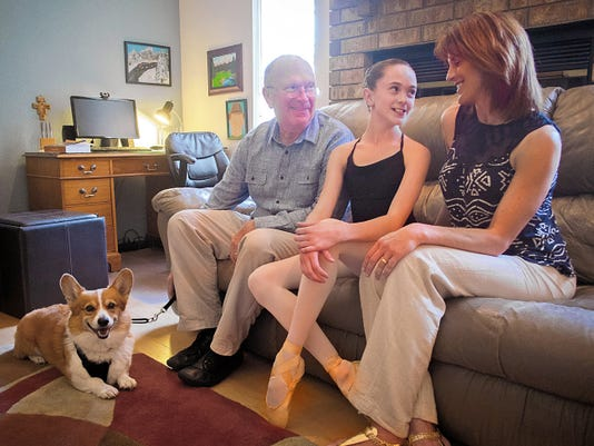 Brigid Walker sits with her father Donald Walker, at left, and mother Jill Walker, along with family Welsh corgi, James Bond, at their Las Cruces home this week. Brigid has a choice of one-year scholarships with top ballet companies in London, Canada, New York and other U.S. sites.
