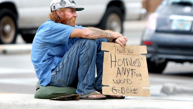 A homeless man sits in the median of Northwest 13th Street in Gainesville Monday.
