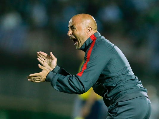 """FILE - In this Nov. 17, 2015, file photo, Chilean soccer team coach Jorge Sampaoli gestures to his players during a FIFA World Cup qualifying soccer match between Uruguay and Chile in Montevideo. Sampaoli says the Argentine soccer federation will negotiate with Spanish club Sevilla to secure his release so he can become the country's national team coach. Sampaoli says """"there is a clear intention by my country to have me as its national coach, and I have had that dream since I was very young."""" (AP Photo/Victor R. Caivano, File)"""