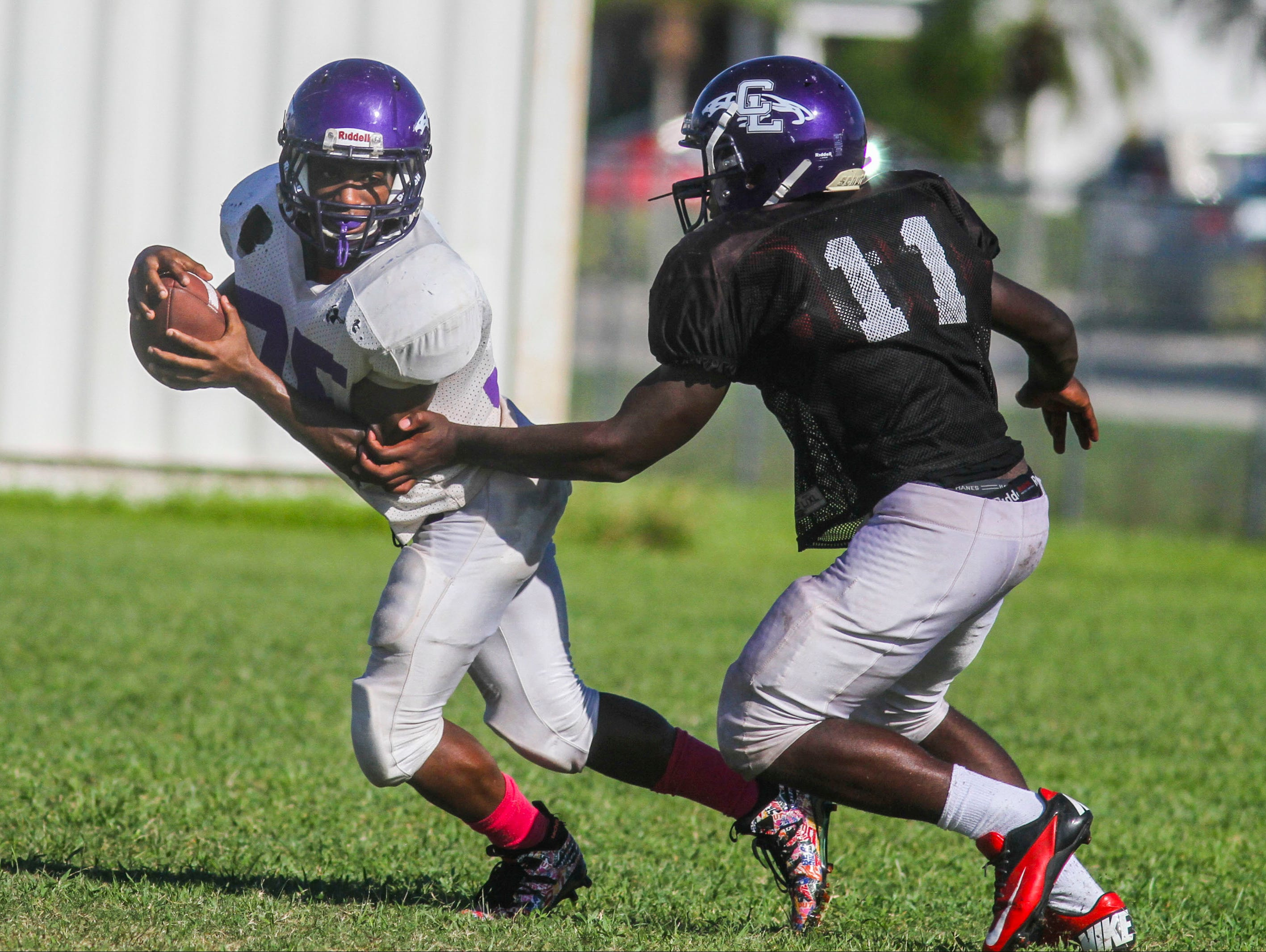 Cliff Moore, running back, for Cypress Lake High School carries the ball as they run plays during football practice Wednesday afternoon.