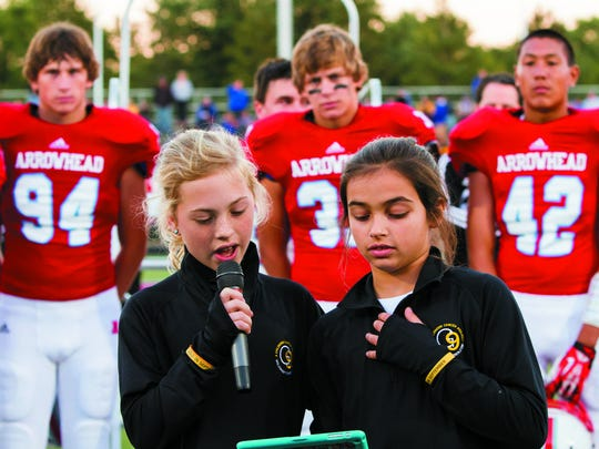 Annie Bartosz (left) of Hartland and friend Olivia Panos address a full stadium at Arrowhead High School before a Sept. 2013 football game. After losing her brother Jack to pediatric cancer, Annie created the Gold In September (G9) Childhood Cancer Project. Annie is determined to turn the world gold in September for kids battling cancer. For more information, visit www.goldinseptember.com.