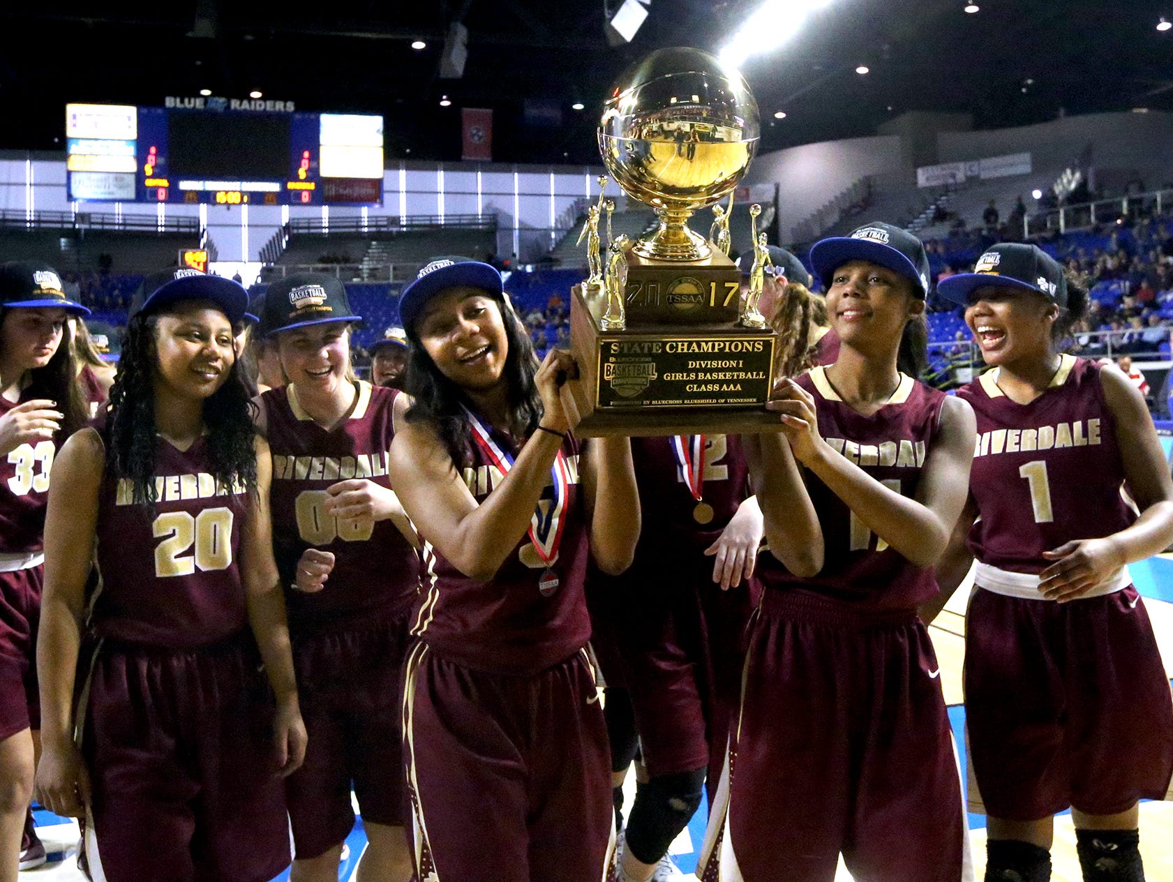 Riverdale's Anastasia Hayes (3) and her sister Aislynn Hayes (11) carry the championship trophy over to the Riverdale fans as the team celebrates its victory over Memphis Central in the Class AAA championship on Saturday, March 11, 2017.