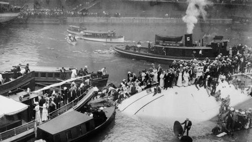 In this July 24, 1915, file photo, passengers are rescued as they stand atop the Eastland passenger ship after the vessel capsized in the Chicago River in downtown Chicago. Film clips have surfaced of the 1915 disaster that left 844 people dead. The first-known footage of the Eastland disaster was spotted by Jeff Nichols, a doctoral student at the University of Illinois at Chicago who was looking through seemingly unrelated material on World War I.
