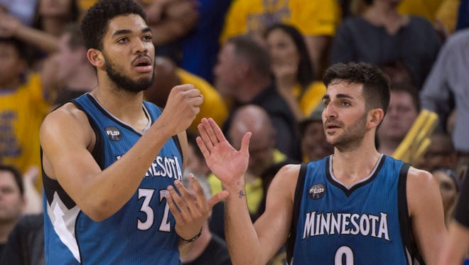 April 5, 2016; Oakland, CA, USA; Minnesota Timberwolves center Karl-Anthony Towns (32) is congratulated by guard Ricky Rubio (9) after making a basket while being fouled against the Golden State Warriors during overtime at Oracle Arena. The Timberwolves defeated the Warriors 124-117. Mandatory Credit: Kyle Terada-USA TODAY Sports