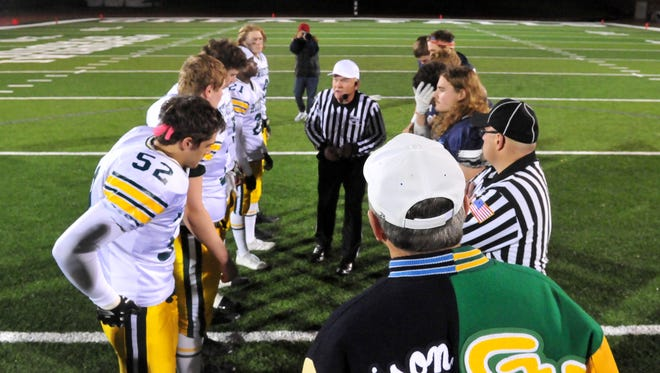 Gary DeGooyer, Athletic Director for Great Falls Public Schools (foreground), watches the coin toss before the crosstown football game between Great Falls High and CMR last November at Memorial Stadium.