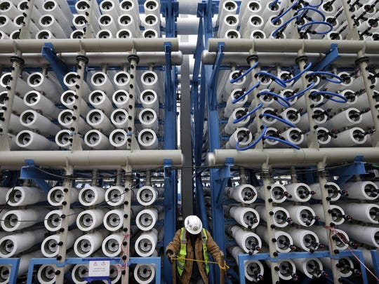 A worker climbs stairs among some of the 2,000 pressure vessels used to convert seawater into fresh water through reverse osmosis in the western hemisphere's largest desalination plant in Carlsbad, Calif.