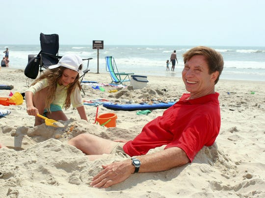 "In this June 8, 2007, file photo, Dr. Stephen Leatherman, aka ""Dr. Beach,"" poses on the beach at Ocracoke, N.C., as Mara Chemerinsky, 8, a visitor from Durham, N.C., plays in the sand."