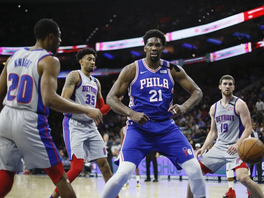 The 76ers' Joel Embiid flexes his muscles after dunking aganst the Pistons on March 11.