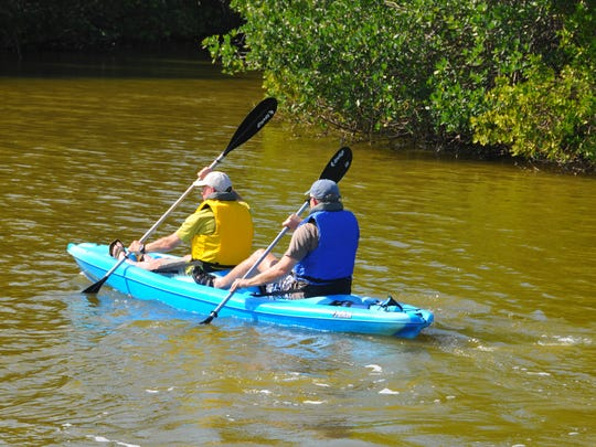 Kayakers paddled in the Thousand Islands area, off of Ramp Road in Cocoa Beach, were the water in the Banana River had a definite brown cast on Wednesday.
