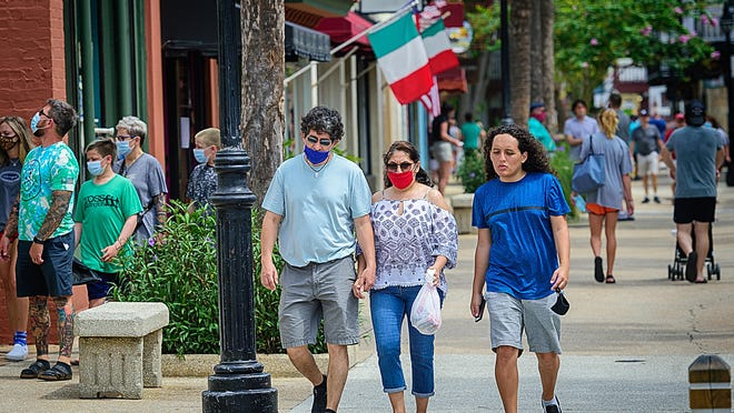 People wearing masks walk down St. George Street in St. Augustine on Monday.