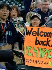 A fan holds a sign welcoming Ichiro Suzuki back to