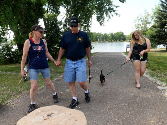 Dave Belcher with his wife, Michelle, and daughter Katie walk along Broadwater Bay on Wednesday. Dave, a Gulf War veteran, suffered a brain injury and PTSD, which lead to the methadone and alcohol dependencies that landed him Veterans Drug Treatment Court. Belcher successfully completed the veterans court program in 18 months.