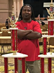 Chess Master of Delaware Coach Greg Rogers stands next to trophies won at the 2017 United States Chess Federation National Elementary Championship.