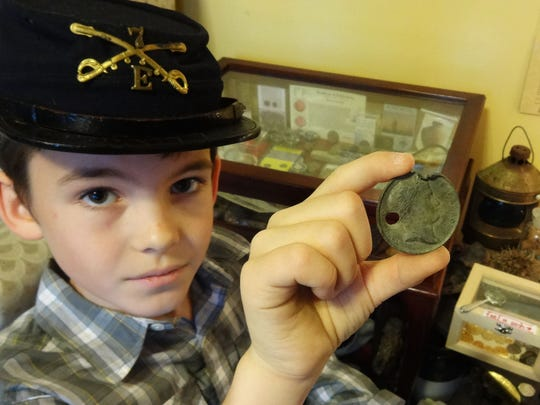 Bobby Grangier holds a French bronze or copper medal minted in 1807 to mark the coronation of Emperor Napoleon. It is believed to have been lost by a British soldier in the Deal Island area during the War of 1812.