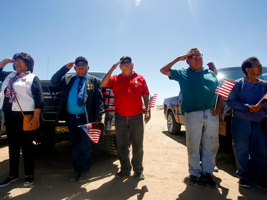 State Rep. Sharon Clahchischilliage, left, and fellow veterans salute during the playing of taps on Monday during a Memorial Day event at the Shiprock Veterans Memorial Cemetery.