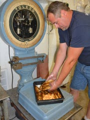 Andy LaFond of LaFond's Fish Market in Kewaunee weights chubs to deliver to The Cannery Public Market in Green Bay.
