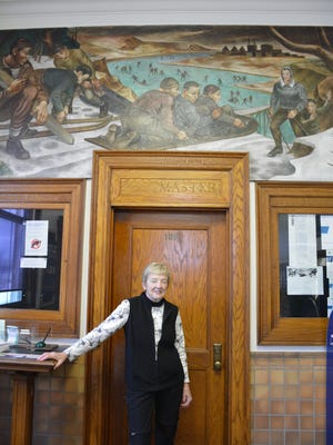 Terry VanPay stands before the door of the postmaster's office in Kewaunee.  Above, is a mural of a winter scene along the river that was painted in the 1930s.