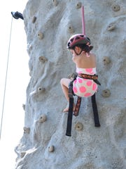 Sophia Holmes, 6, of Clayton descends after climbing the rock wall at the Richland Village Festival. Photo/Jodi Streahle