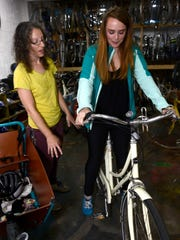 "Michelle Gross, 21, picks a bike to rent with help from Revolutions Co-op founder, Sylvia Crum.  ""It's my first time renting here and my second time riding in Midtown,"" Gross said. ""I feel more comfortable doing it with a group because [riding alone in Midtown] was kind of scary."""